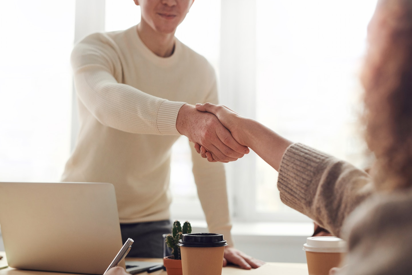 job candidate shaking hands with HR manager at job interview