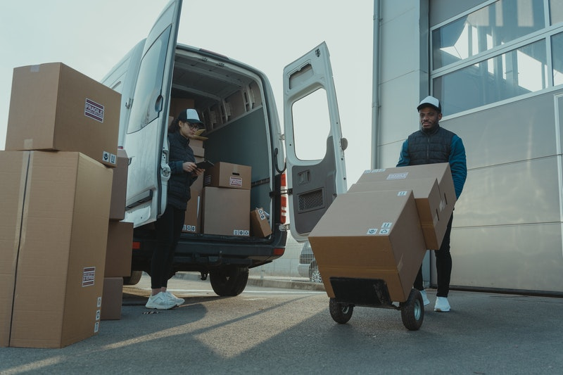 warehouse workers loading truck with parcels